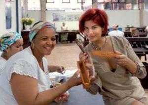 Stolz präsentiert Indira ihre selbst gerollte Zigarre und das personalisierte Holzkistchen, in dem sie aufbewahrt wird.