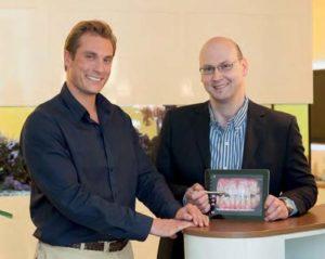 Dr. Axel Raymond Spittler und P. Tomovic demonstrieren die innovative Präsentation der Behandlungsplanung. Die überlagerten weißen Umrisse auf dem iPad-Bild zeigen die Idealform der Oberkiefer-Frontzähne.