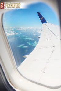 Die Inselwelt der Malediven beeindruckt schon durch das Fenster des Condor-Flugzeugs.