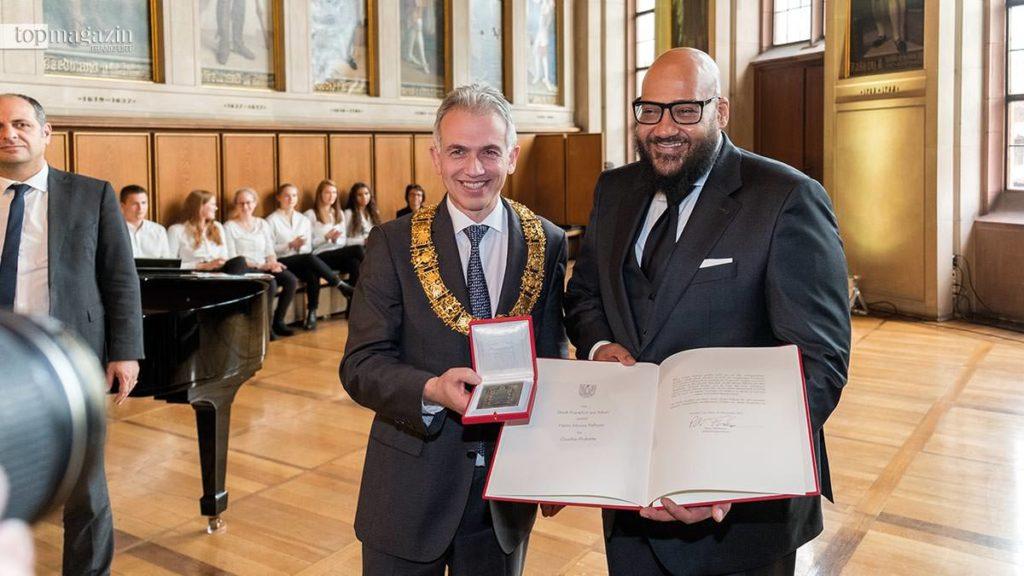 Oberbürgermeister Peter Feldmann überreicht Moses Pelham die Goethe-Plakette.