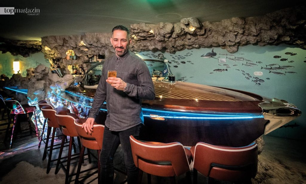 Barchef Farid Rahimi vor dem als Barthresen fungierenden Riva-Boot