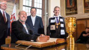 Eintracht-Präsident Peter Fischer trägt sich unter den Augen von Bürgermeister Uwe Becker, Stadtverordnetenvorsteher Stephan Sieger und Oberbürgermeister Peter Feldmann ins Goldene Buch der Stadt ein.