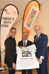 EURO-Botschafter Fredi Bobic, Oberbürgermeister Peter Feldmann und Stadtrat Markus Frank zeigen ein Trikot mit der Aufschrift 'Host City UEFA EURO 2024 Frankfurt am Main'