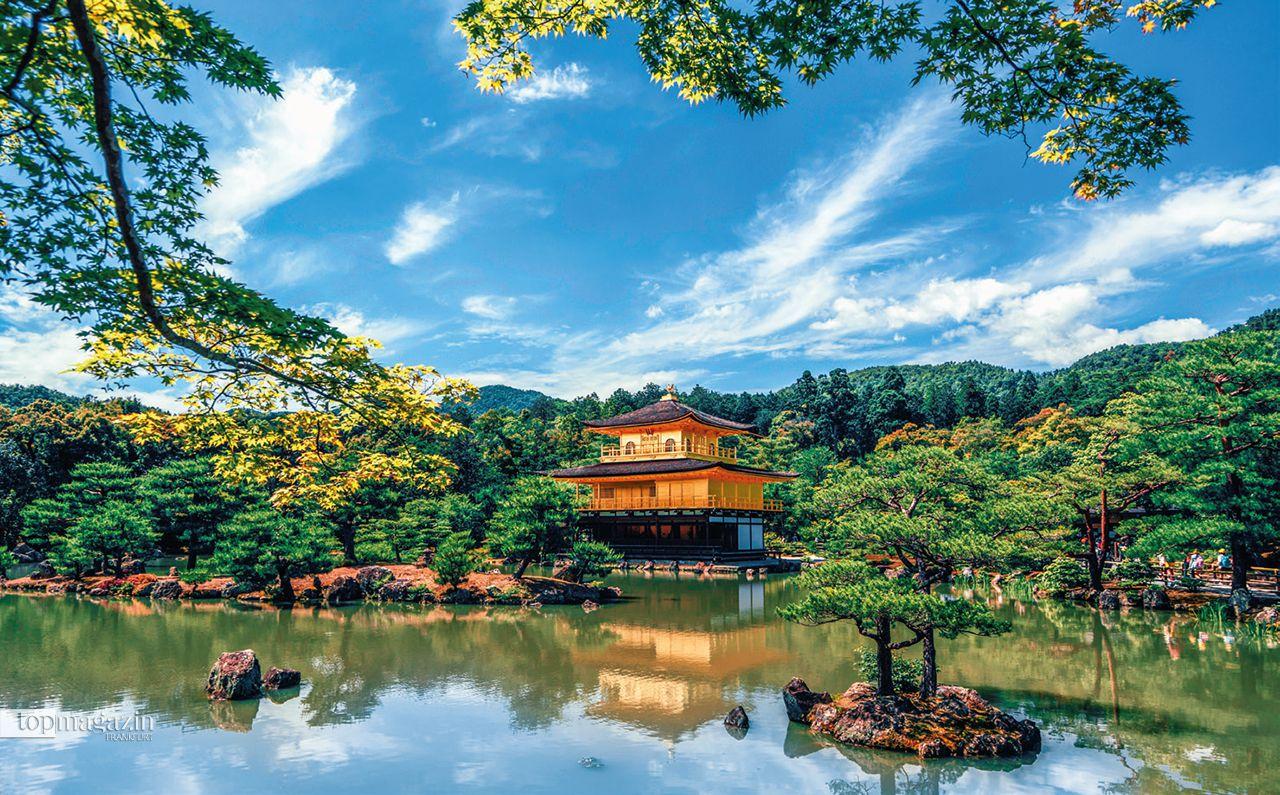 """Kinkaku-Ki, Kyoto Japan: Der """"Goldene Pavillon"""" ist eingebettet in seine natürliche Umgebung und liegt am Rande eines großen Sees. Er schmiegt sich dezent an die von Bäumen und Sträuchern geprägte Parklandschaft an und symbolisiert die harmonische Beziehung zwischen Mensch und Natur."""